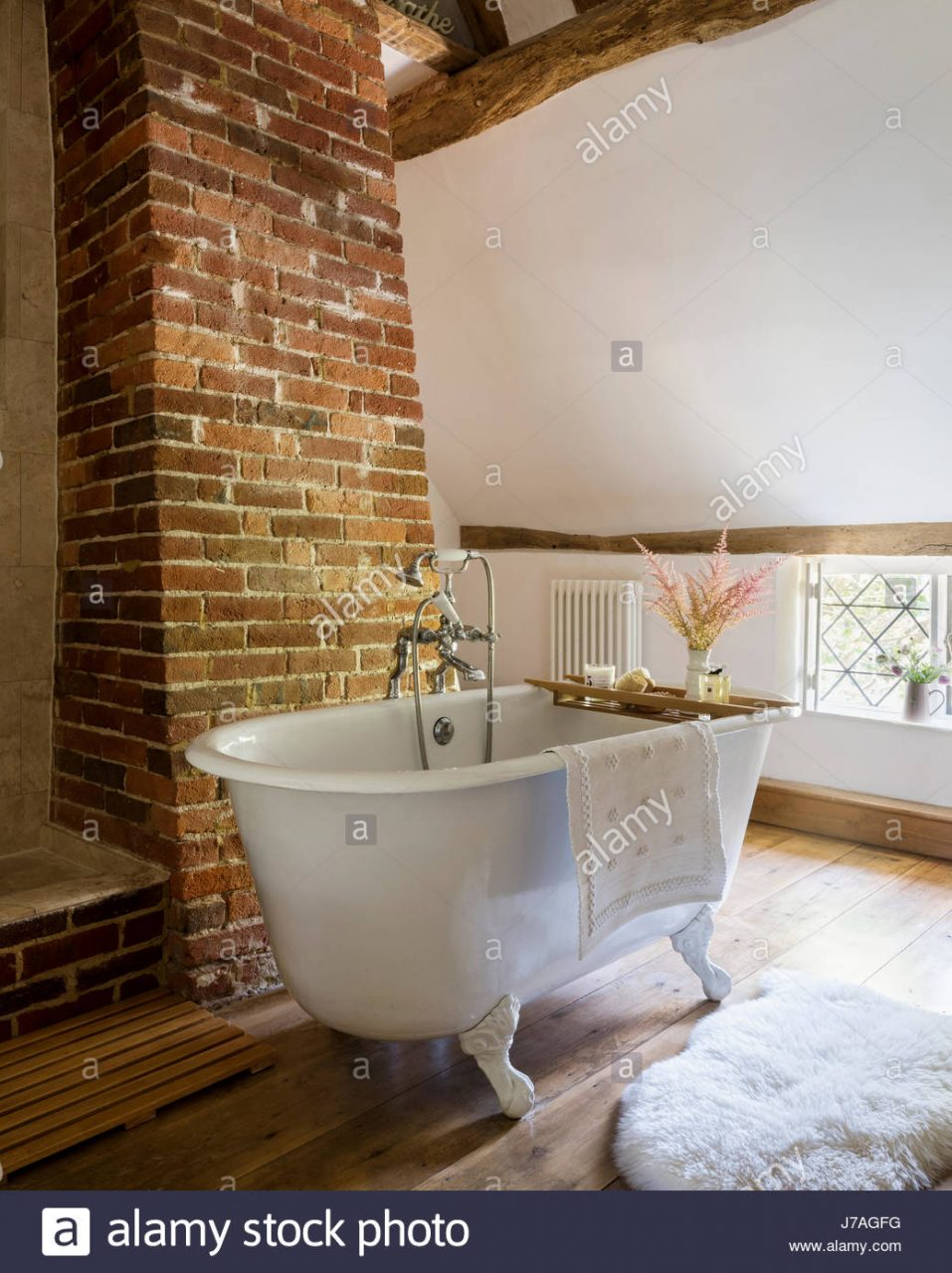 Vaulted Bathroom With Ancient Beams Exposed Brick Wall And Roll Top