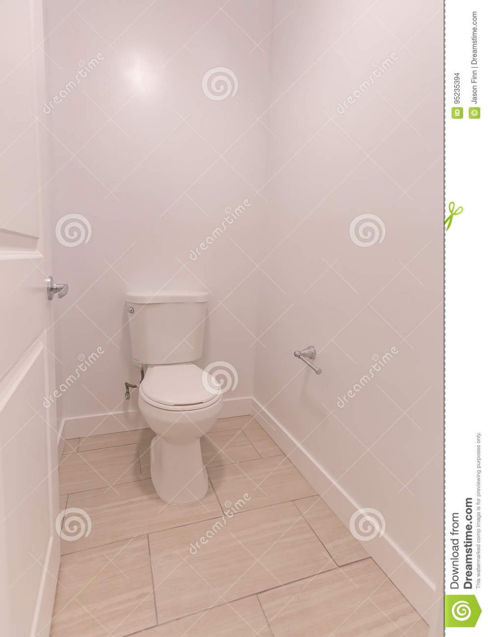 White Corner Toilet In Bathroom With Tan Tiles And White Walls In