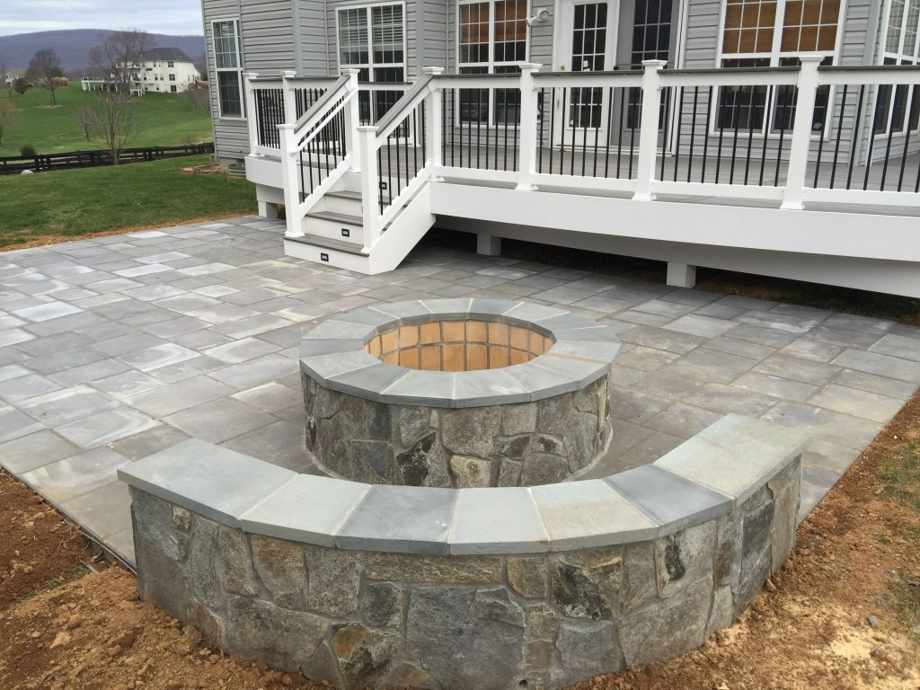 A Beautiful Paver Patio With Stone Seating Walls And A Fire Pit