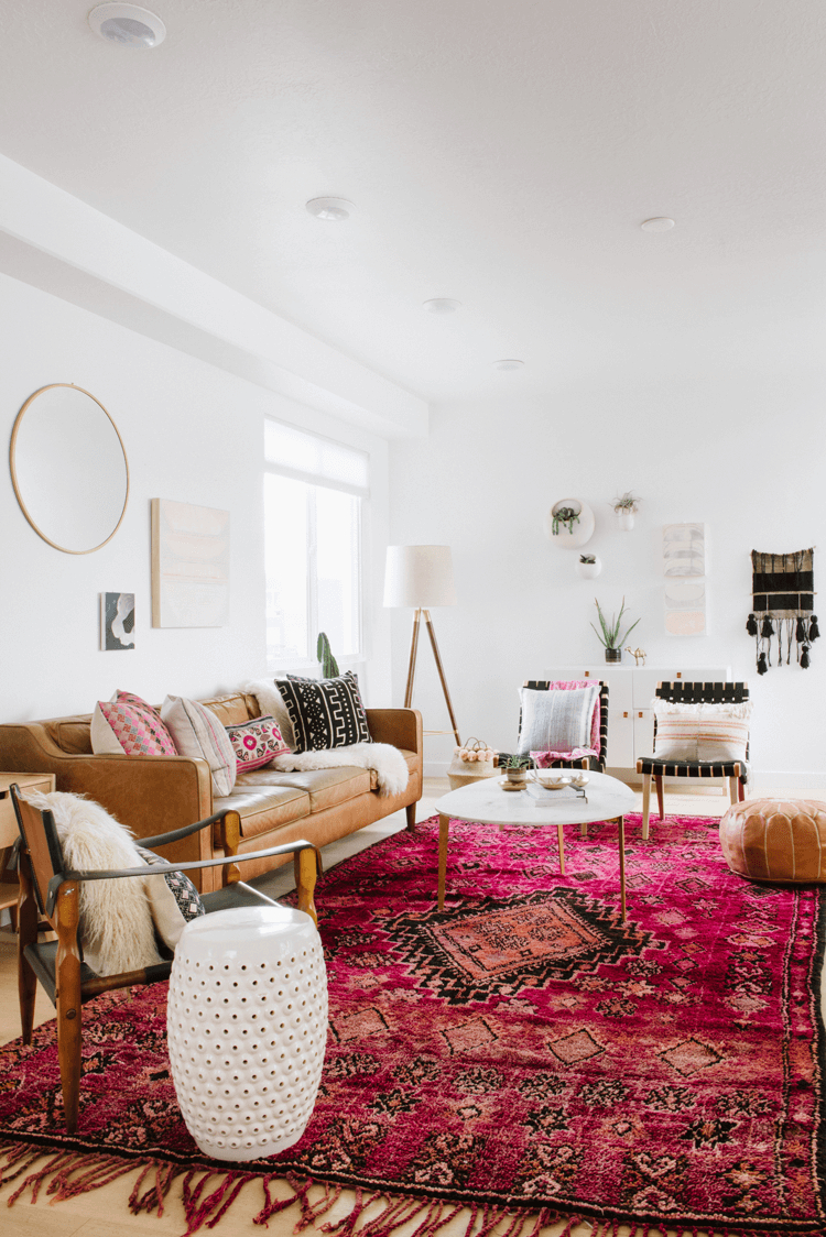 A Vintage Living Room With Pink Rug And Tan Leather Pouf Pantone