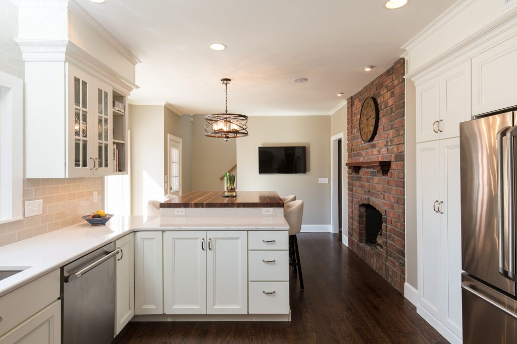 A Warm White Kitchen With An Exposed Brick Fireplace The Cambria