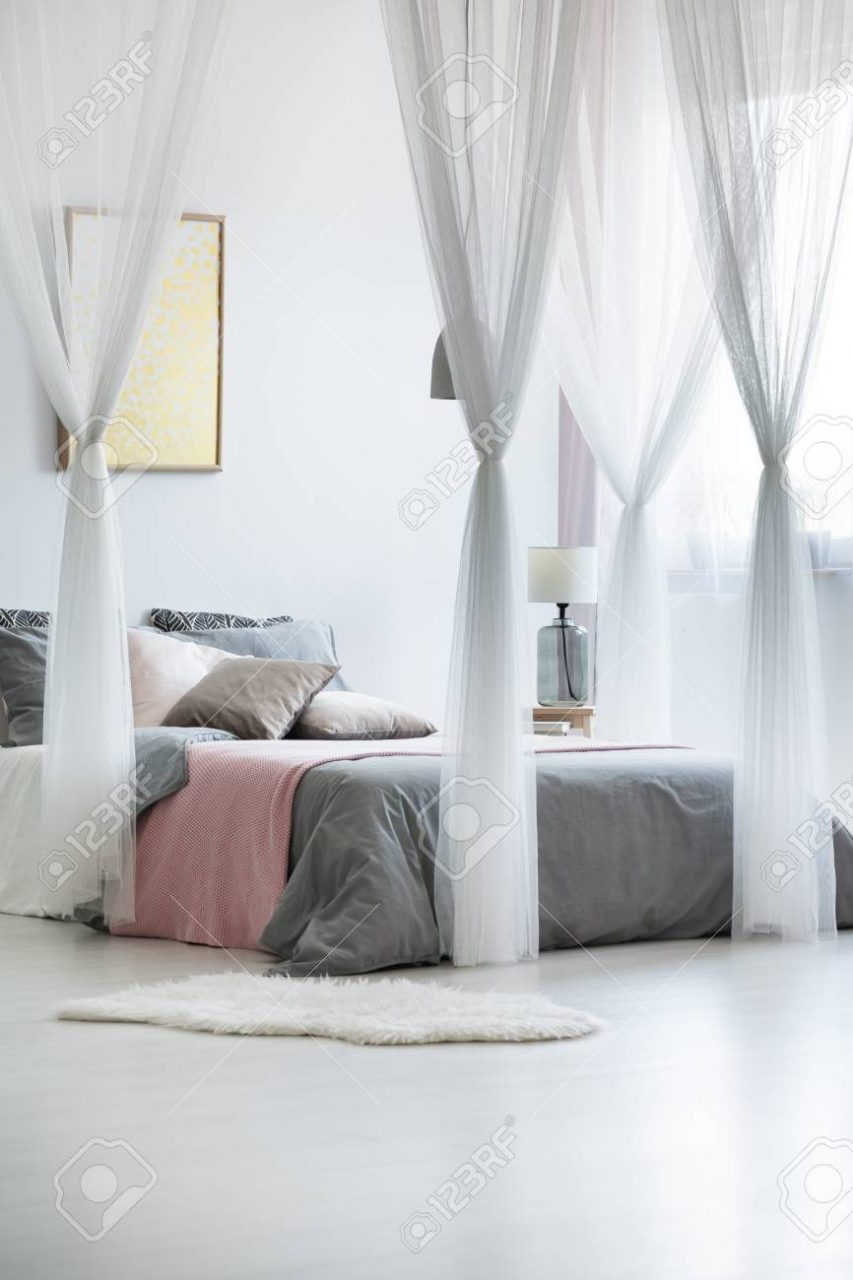 Artwork Above King Size Bed With Canopy Bed Drapes And Light