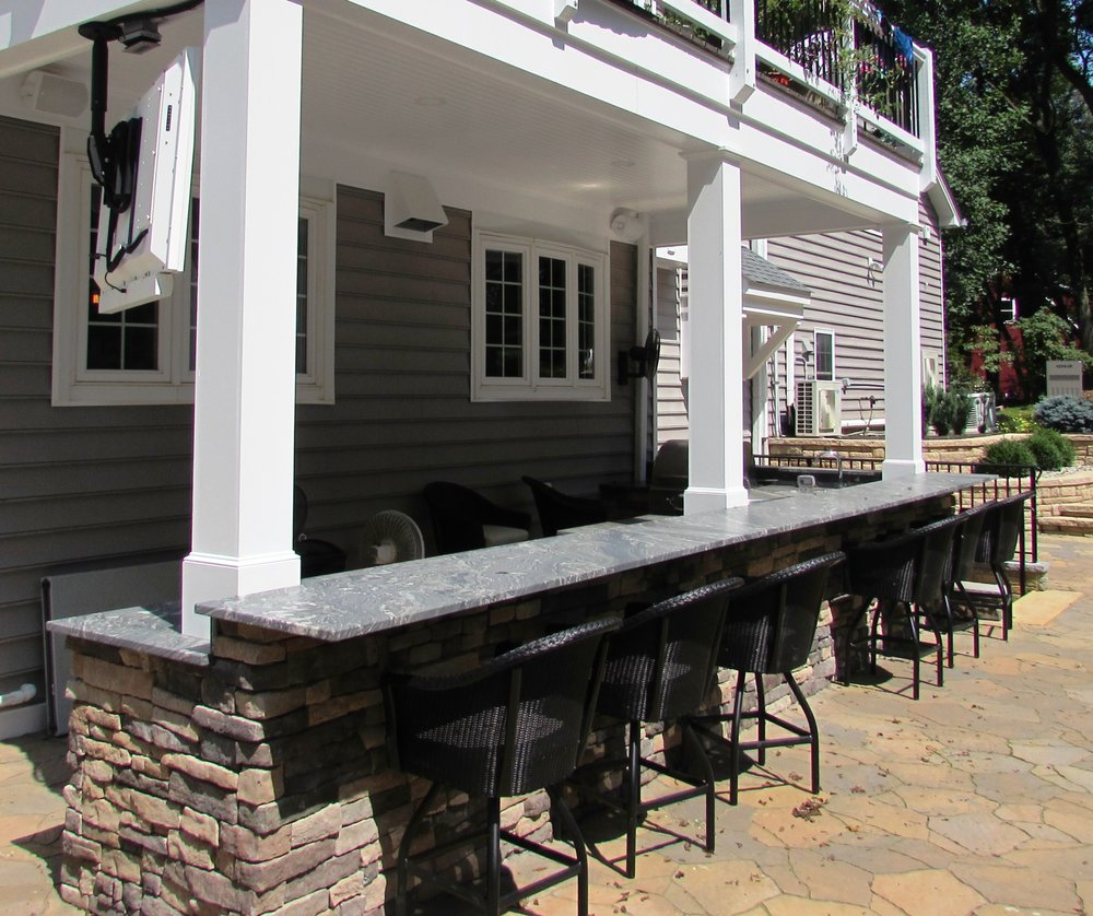 Back Yard Outdoor Living Space With Kitchen And A Bar With Tv In