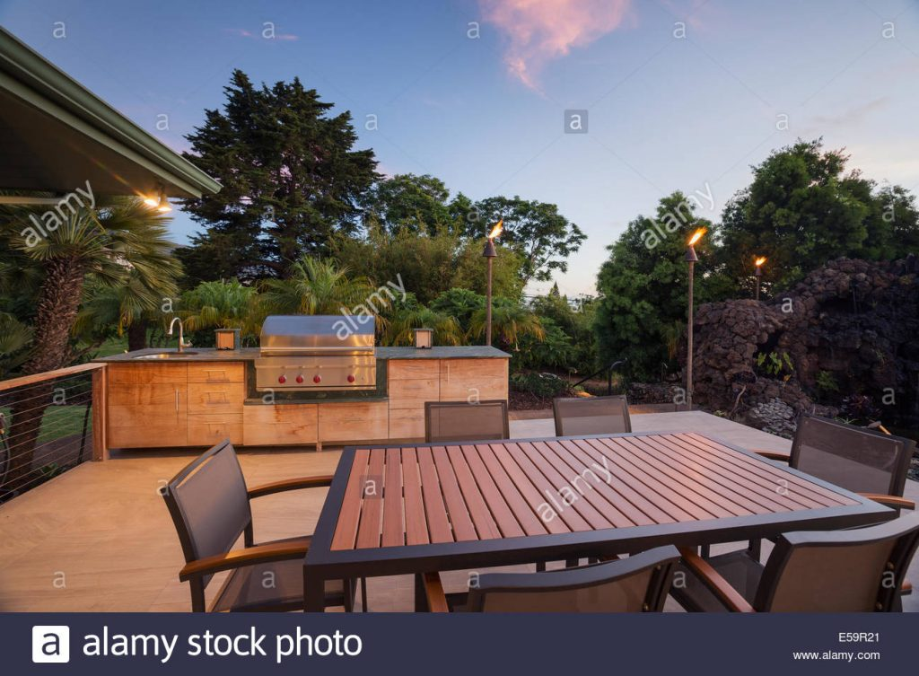 Backyard Patio With Bbq Grill And Dining Table On Deck Stock Photo