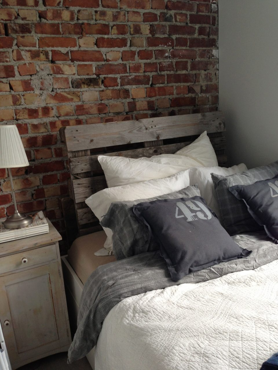Brick Wall Pallet Headboard Vintage Nightstand And Gray Bedsheets