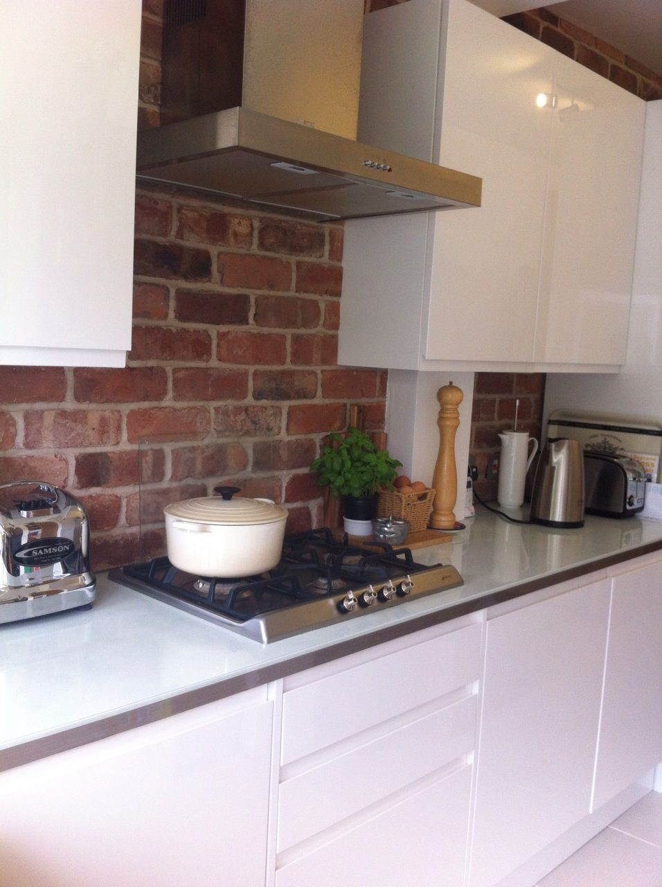 Exposed Brick Kitchen With Clean Gloss White Units White Kitchens