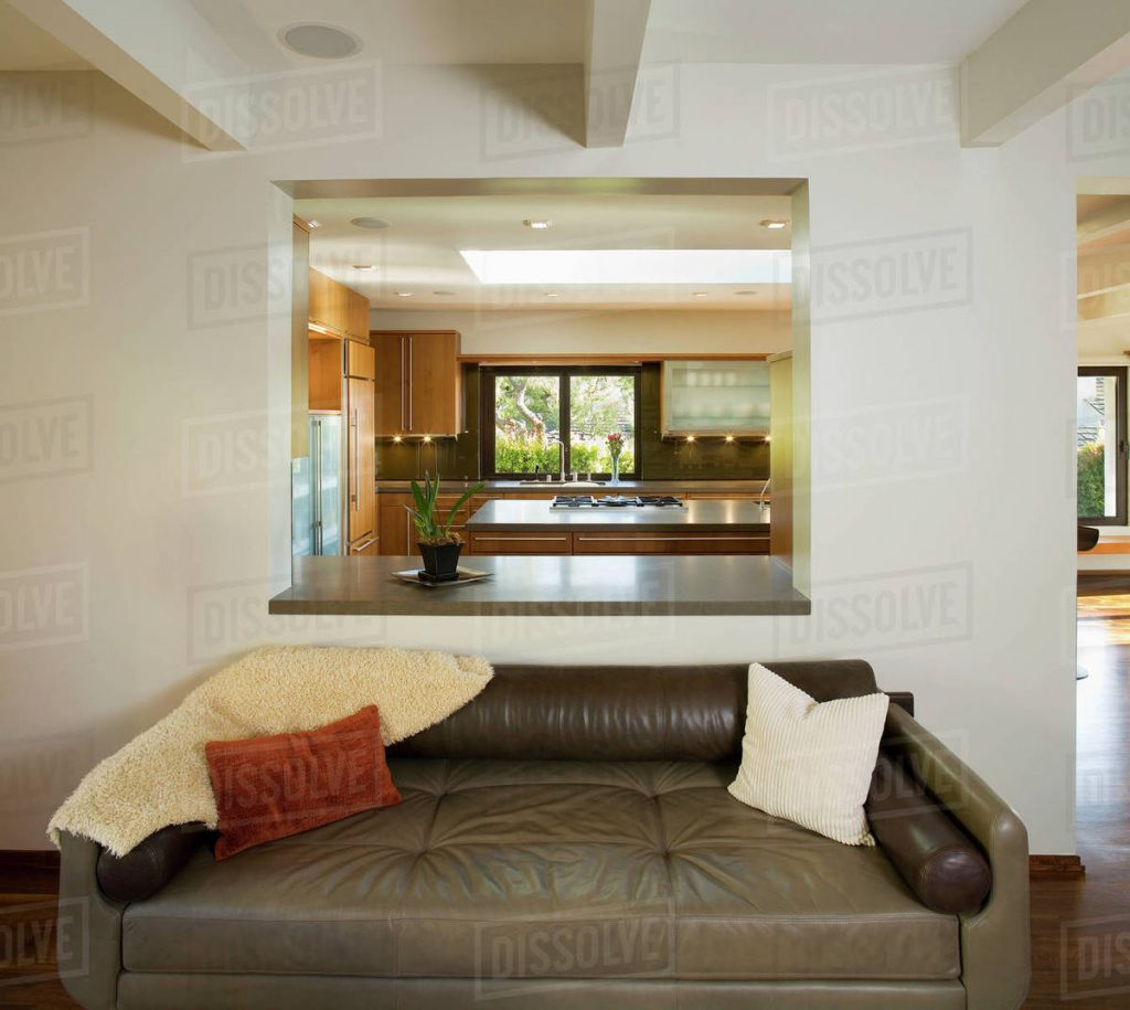 Leather Sofa In Modern Living Room With Cutout To Kitchen Stock Photo