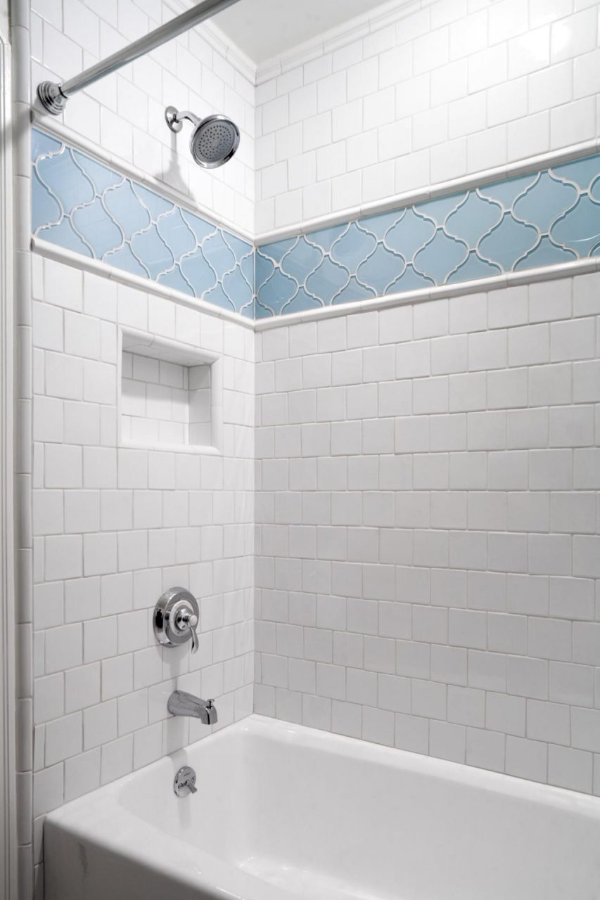 This Traditional White Tile Shower Features A Blue Patterned Accent